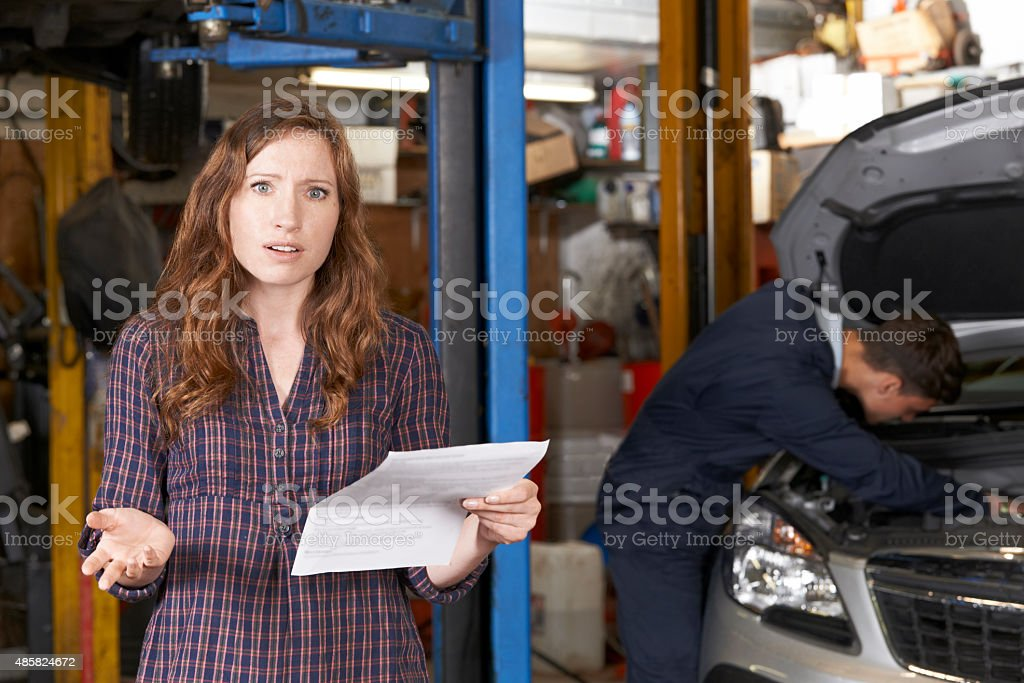 Shocked Female Customer Looking At Garage Bill stock photo