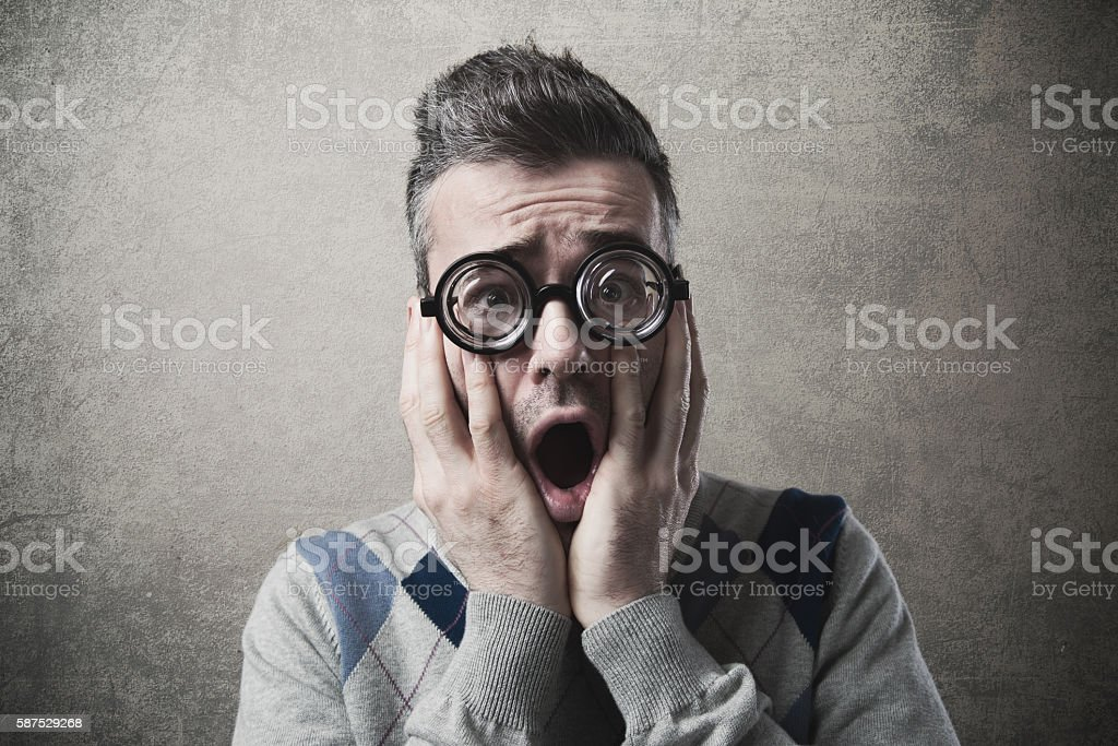 Shocked funny guy with head in hands stock photo