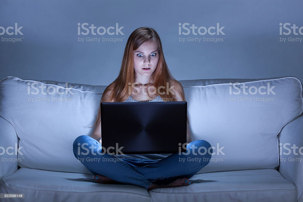 Shocked girl using computer at night stock photo