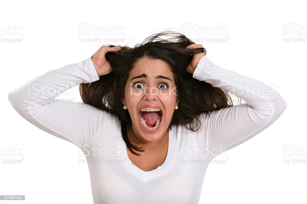 Shocked Hispanic young woman tearing hair out and screaming stock photo