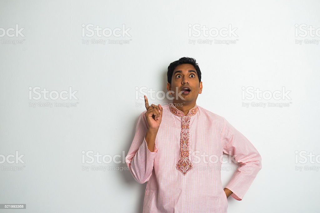 shocked indian male in traditional clothing and plain background stock photo