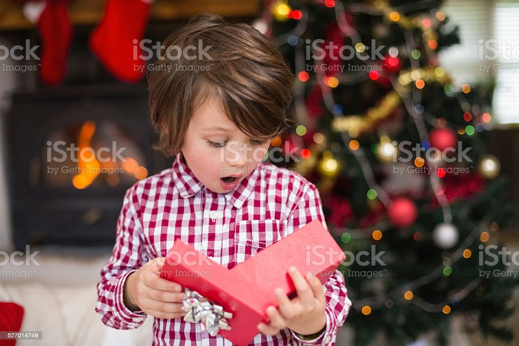 Shocked little boy looking at gift stock photo
