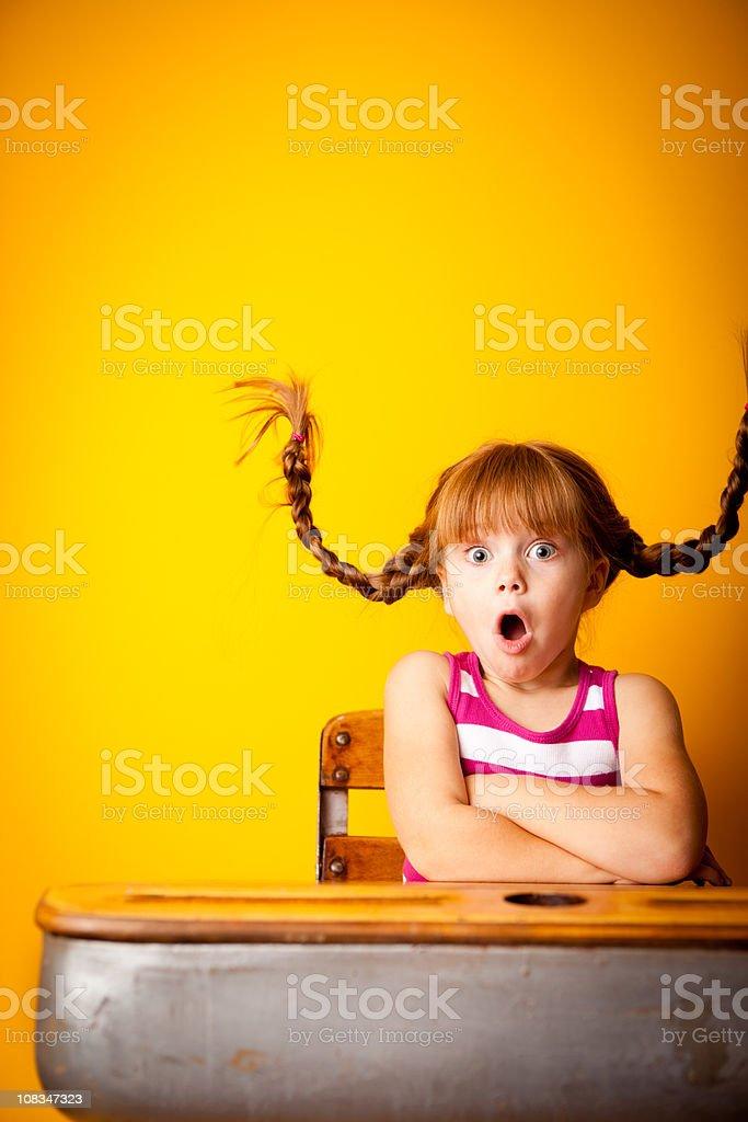 Shocked Little Girl with Upward Braids Sitting in School Desk stock photo