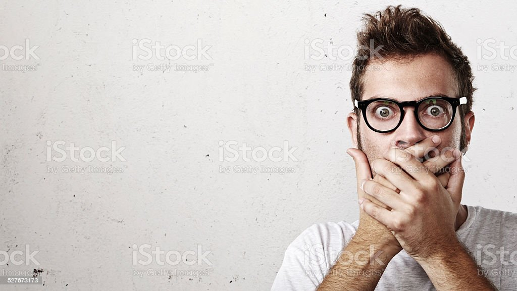 Shocked man covering his mouth with hands stock photo