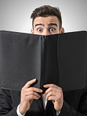 Shocked man expressive eyes reading restaurant menu prices.