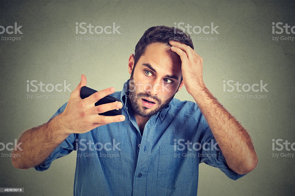 shocked man feeling head, surprised losing hair, receding hairline stock photo