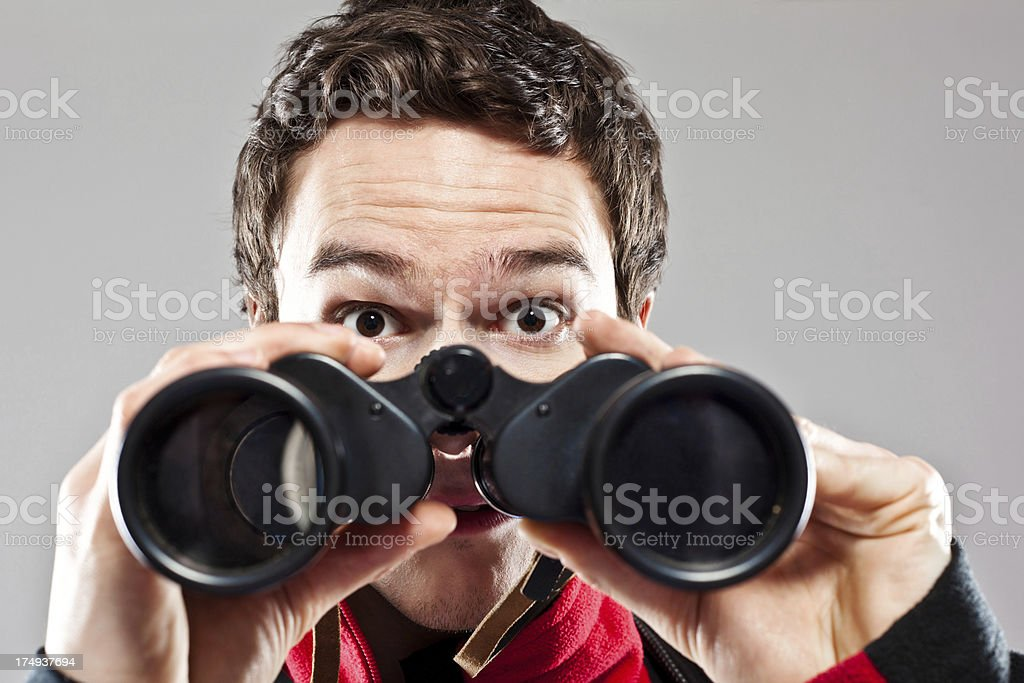 Shocked man holding binoculars royalty-free stock photo