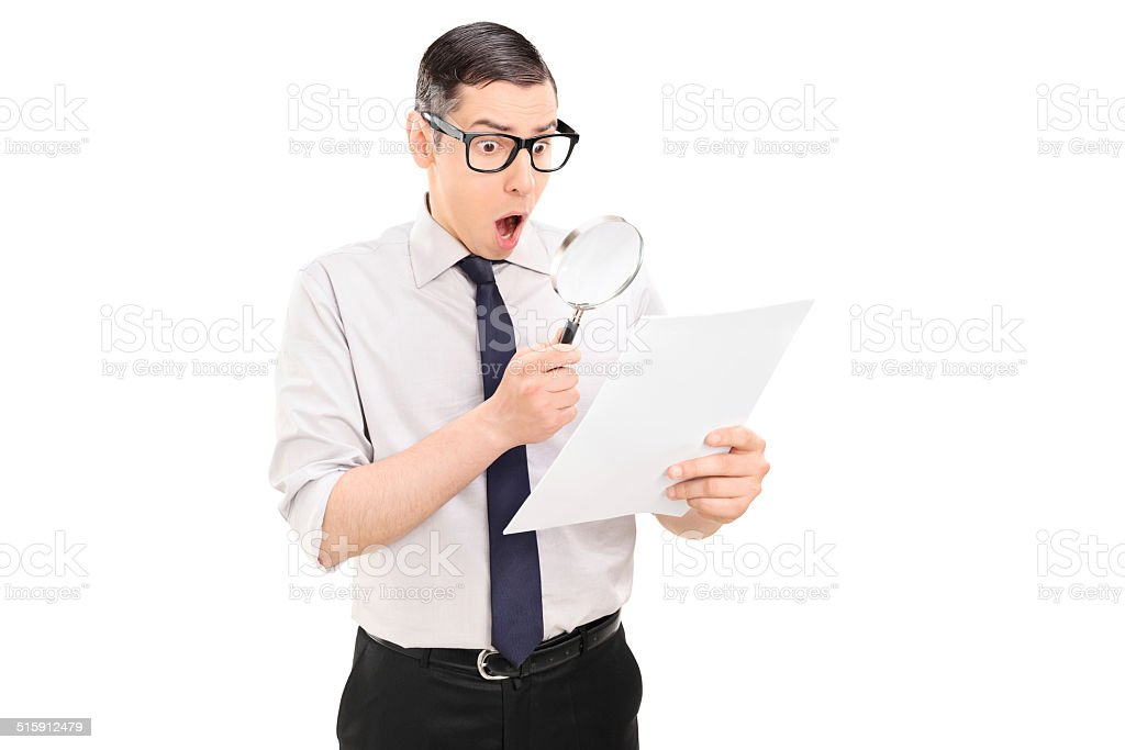 Shocked man looking at document through magnifier stock photo