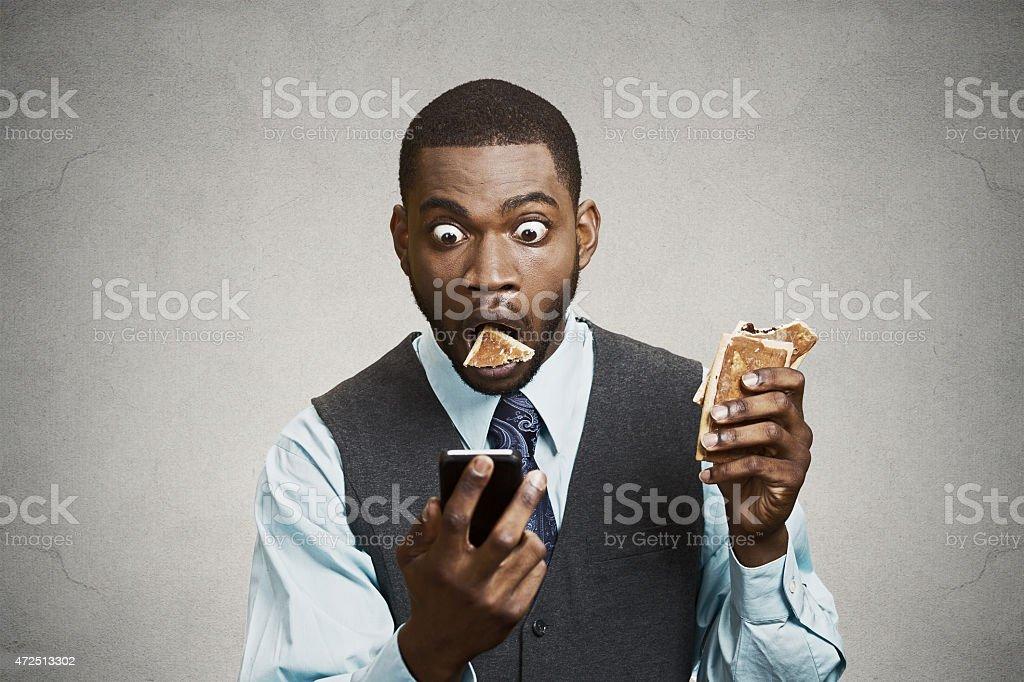 Shocked Man reading news on Phone while eating stock photo