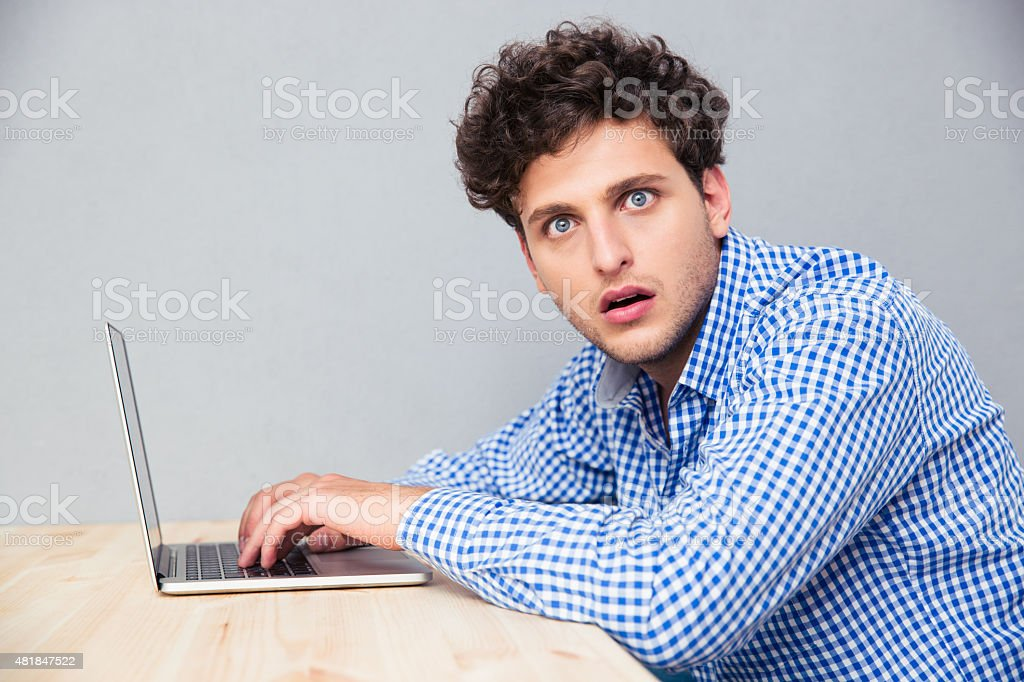 Shocked man sitting at the table with laptop stock photo