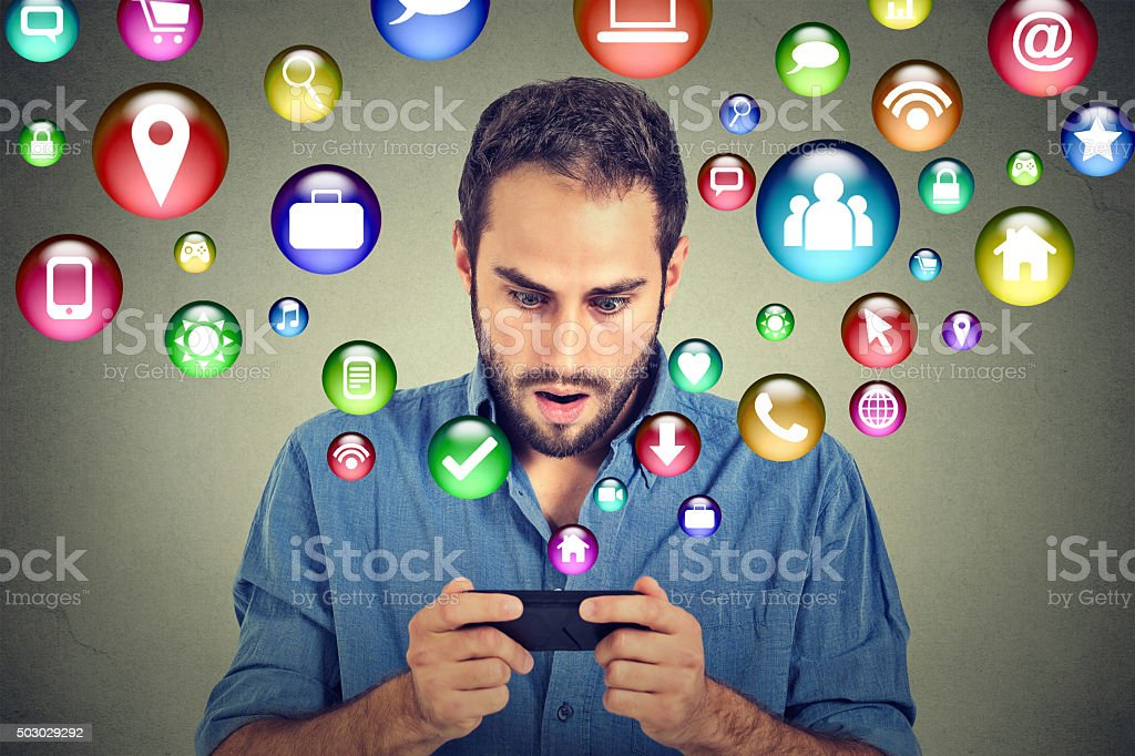 Shocked man texting on smartphone application icons flying out stock photo