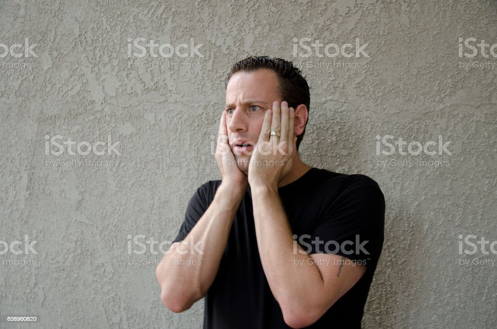 Shocked man with hands on his face. stock photo