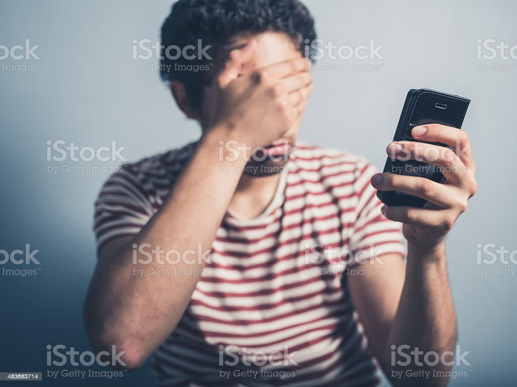 Shocked man with smart phone stock photo