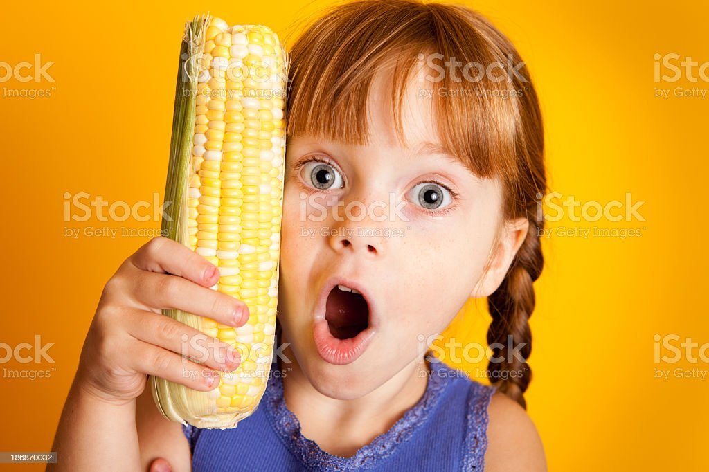 Shocked Red-Haired Girl Holding Corn on the Cob royalty-free stock photo