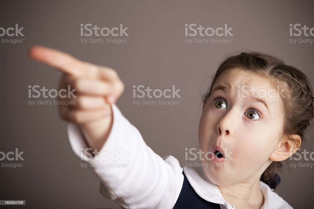 Shocked Student Girl in School Uniform Pointing at Something royalty-free stock photo