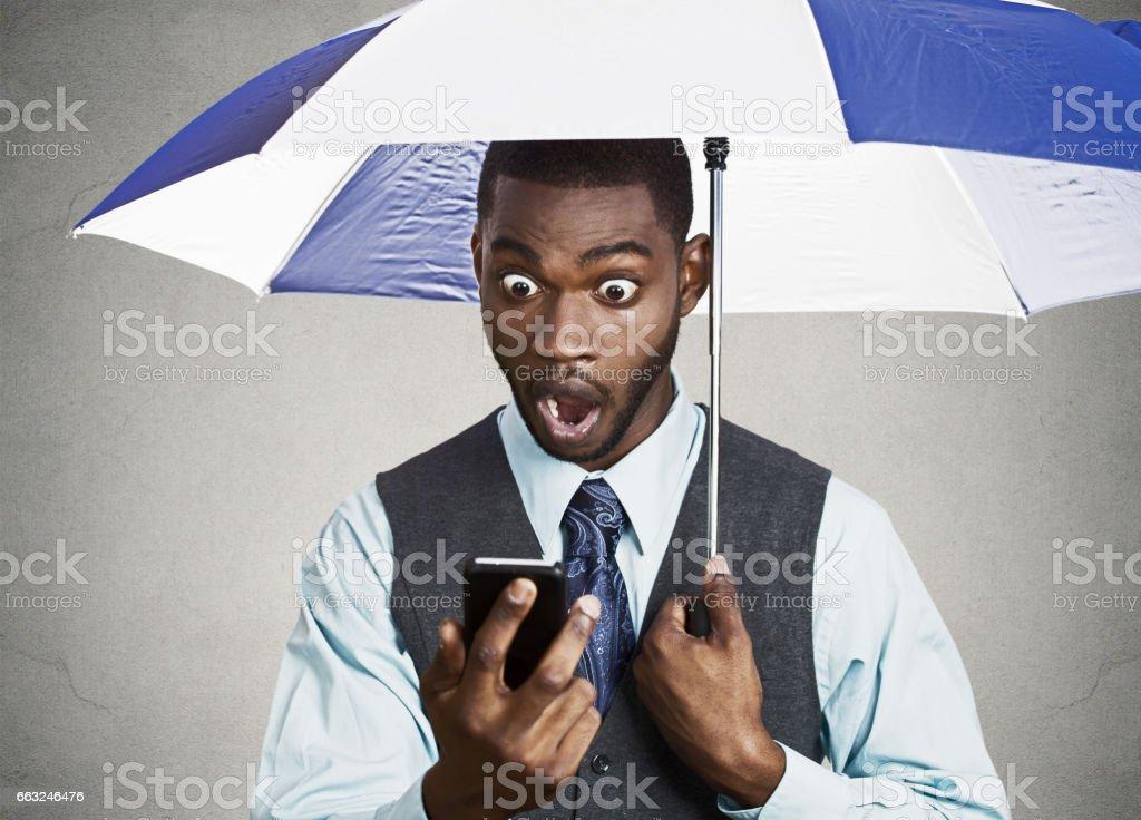 shocked, surprised business man, corporate executive reading bad, breaking news on smart phone holding umbrella stock photo