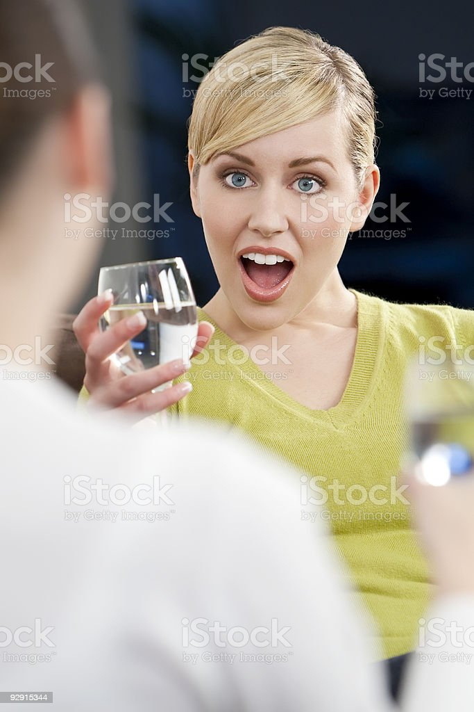 Shocked Surprised Young Blond Woman Drinking With A Friend royalty-free stock photo