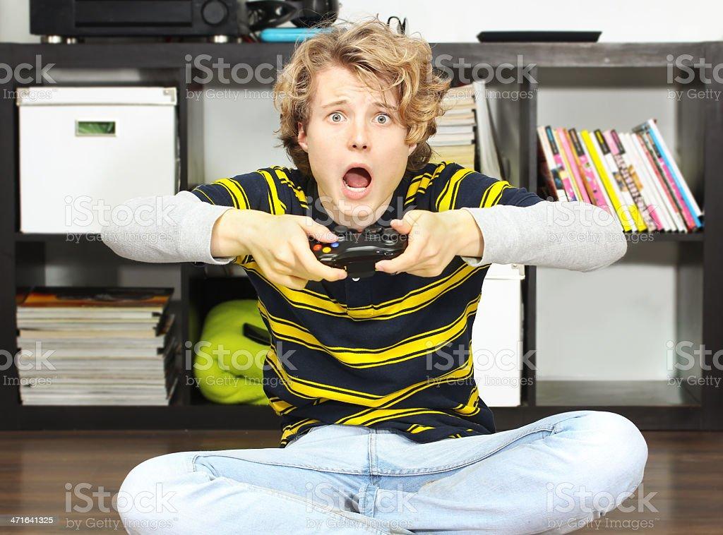 Shocked teenage boy  playing  game royalty-free stock photo