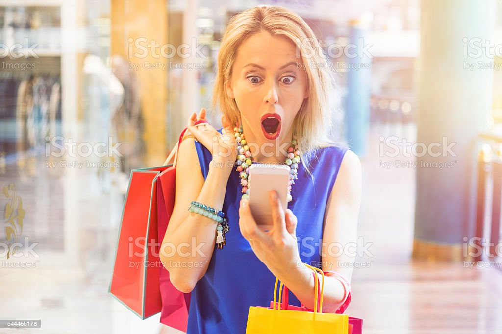 Shocked woman at the shopping mall looking at the phone stock photo