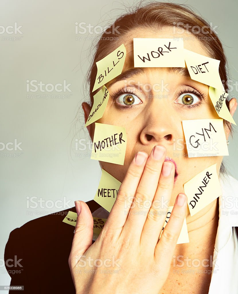 Shocked woman covered in task-reminder adhesive notes stock photo
