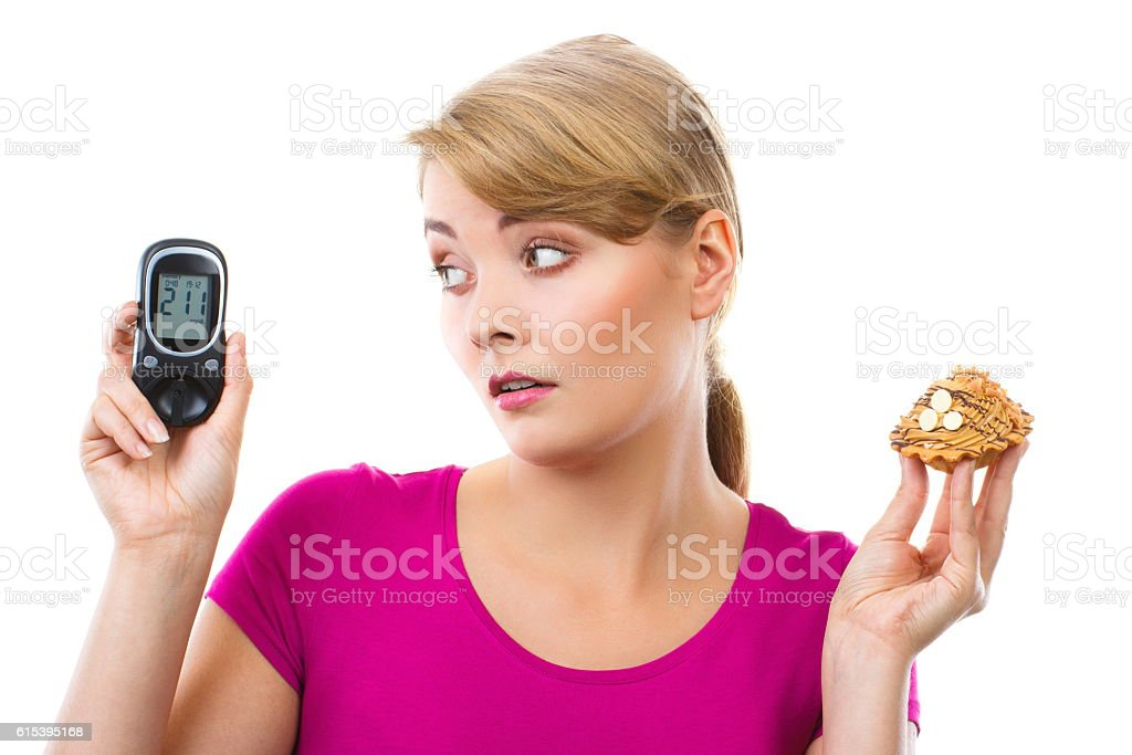 Shocked woman holding glucometer and fresh cupcake stock photo