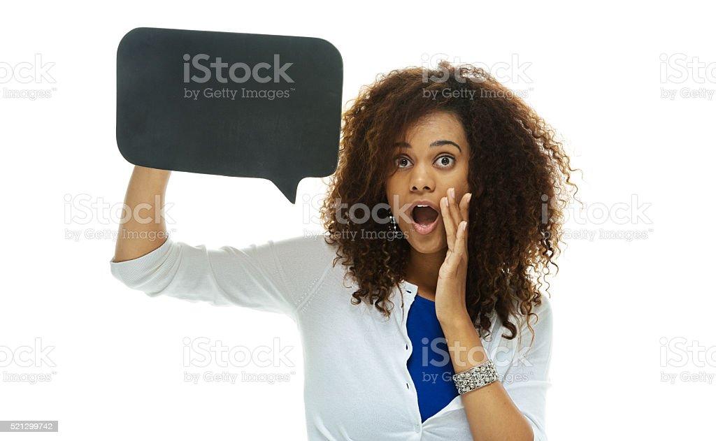 Shocked woman holding speech bubble stock photo