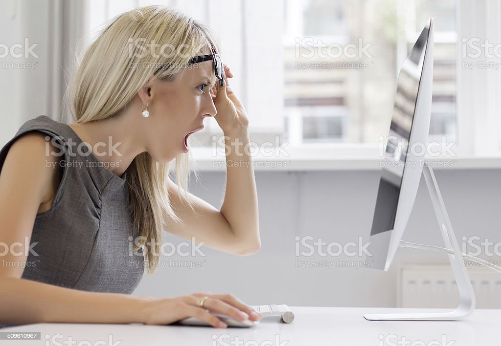 Shocked woman looking at computer screen with totally surprised look stock photo