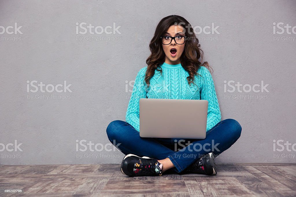 Shocked woman sitting on the floor with laptop stock photo