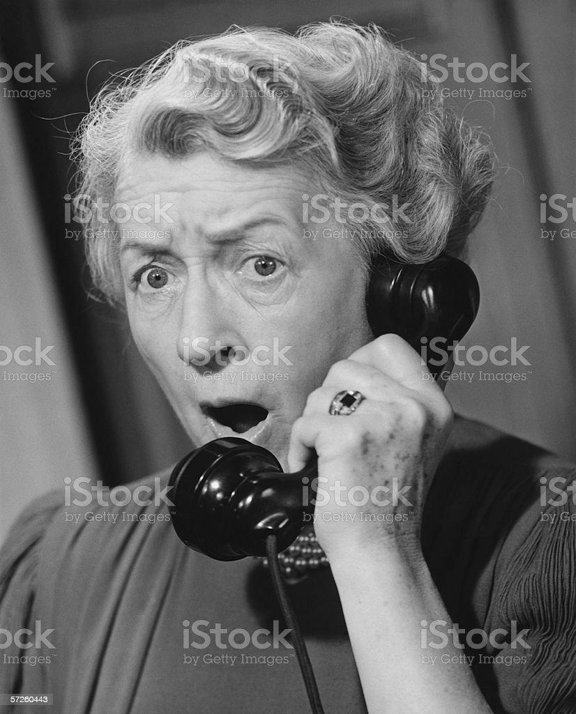 Shocked woman using phone, (B&W), close-up royalty-free stock photo