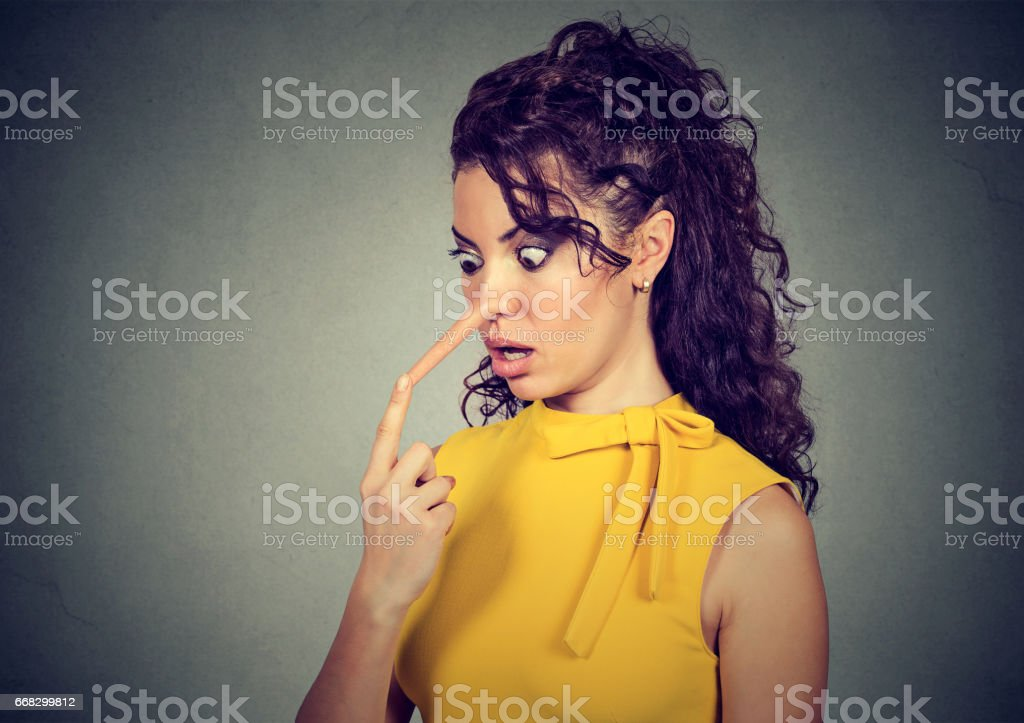Shocked woman with long nose isolated on gray wall background. Liar concept stock photo