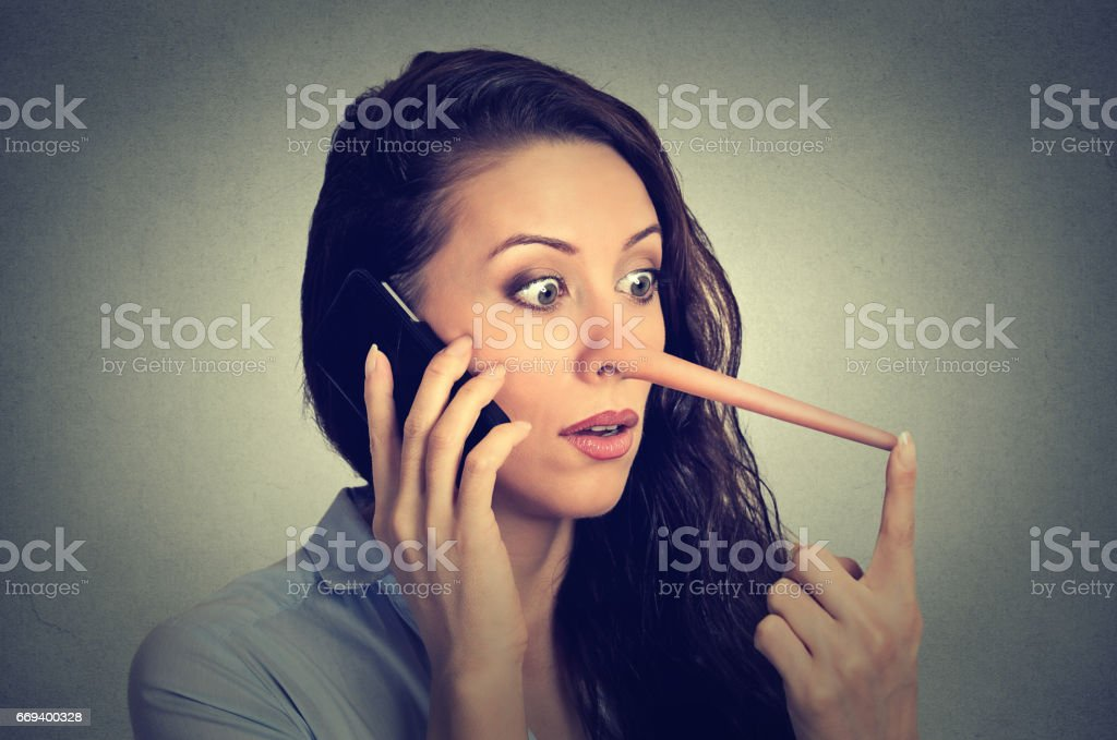 shocked woman with long nose talking on mobile phone isolated on grey wall background. Liar concept. stock photo