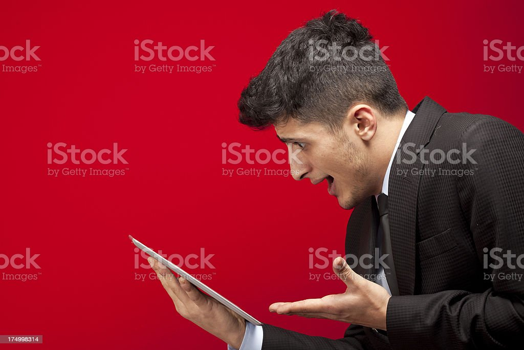 Shocked Young Businessman Looking at Tablet Pc royalty-free stock photo