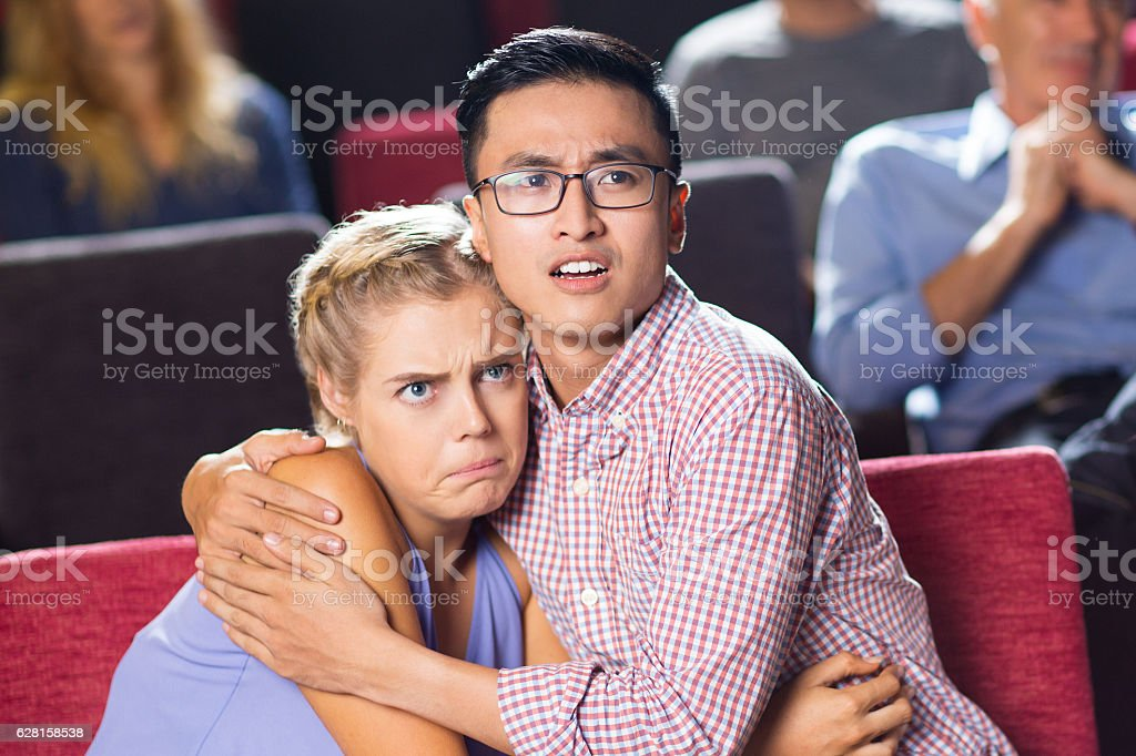 Shocked young couple watching horror in cinema stock photo