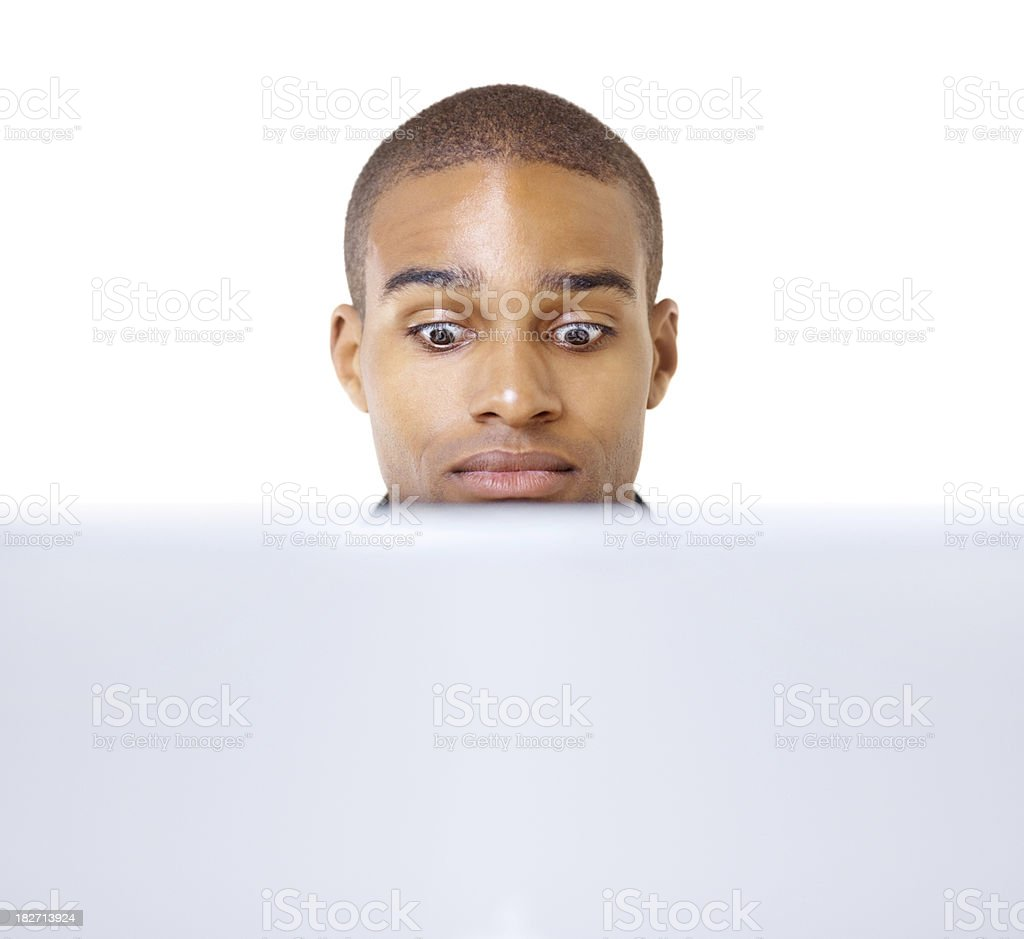 Shocked young guy using a laptop royalty-free stock photo