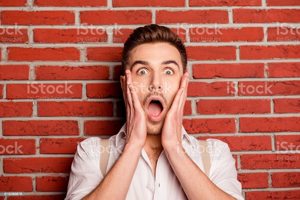 Shocked young man touching his face stock photo