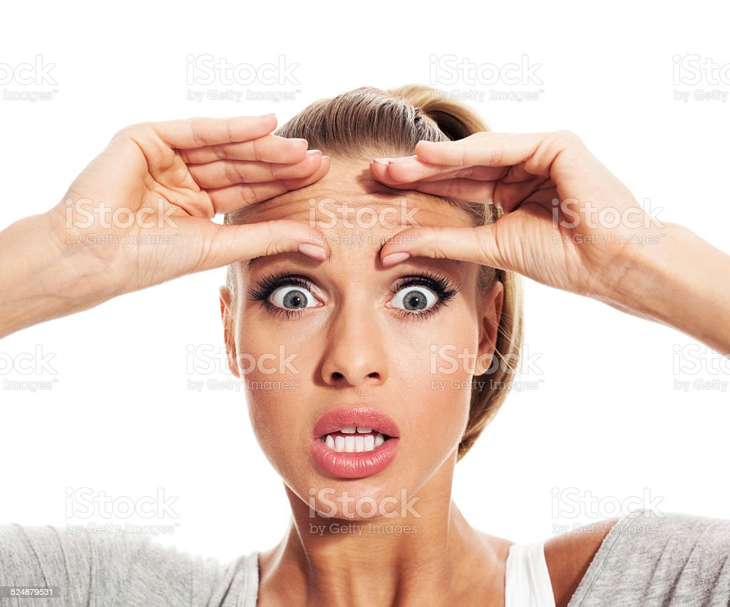 Shocked young woman checking her wrinkles stock photo