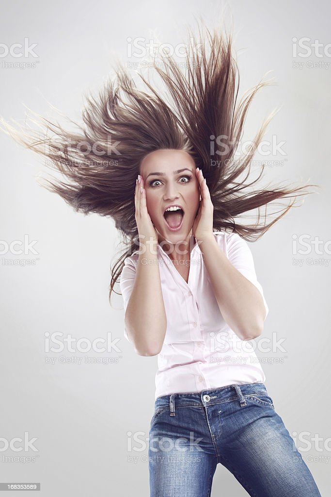 Shocked young woman with hair up in the air stock photo