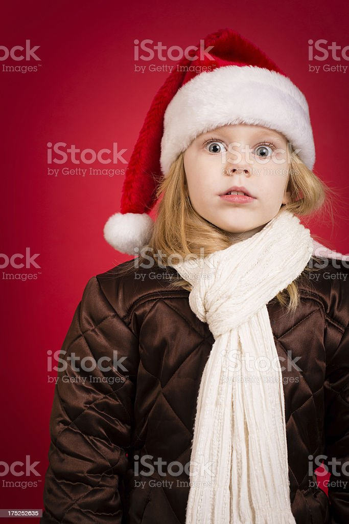 Shocked/Stressed Little Girl Wearing Santa Hat, With Red Background royalty-free stock photo