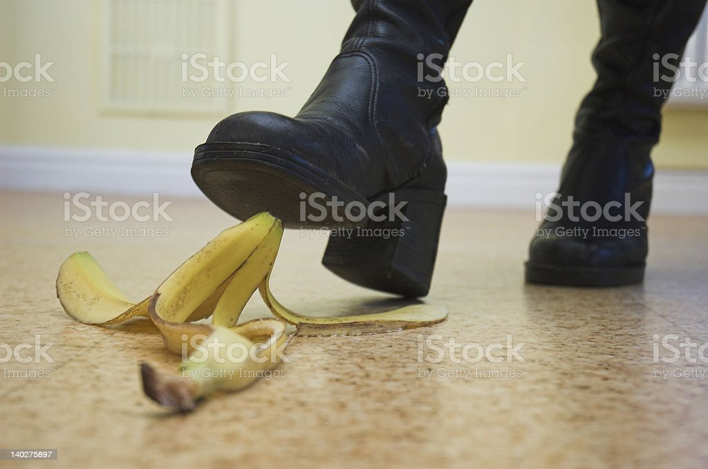 A shoe about to step on a banana peel on the floor royalty-free stock photo