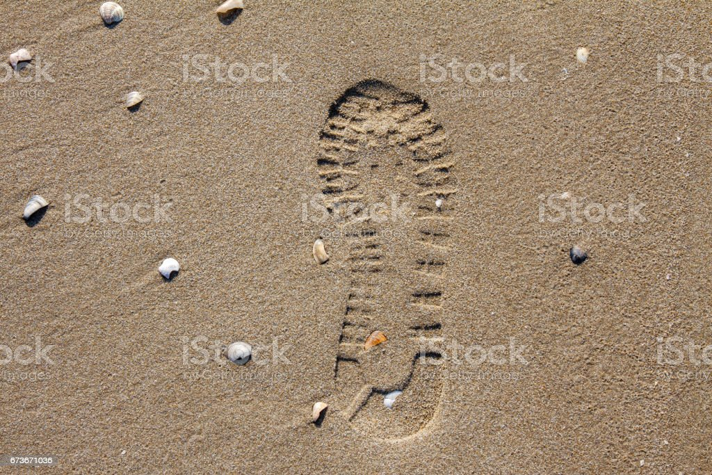 Shoe imprint in the sand of a beach stock photo