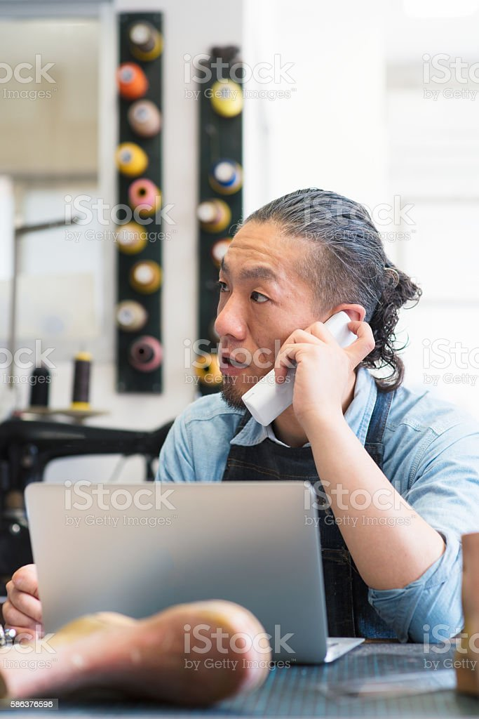 Shoe maker talking on the phone and using a computer stock photo