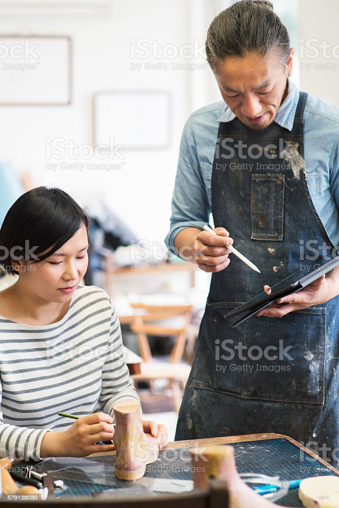 Shoe maker talking with a colleague stock photo