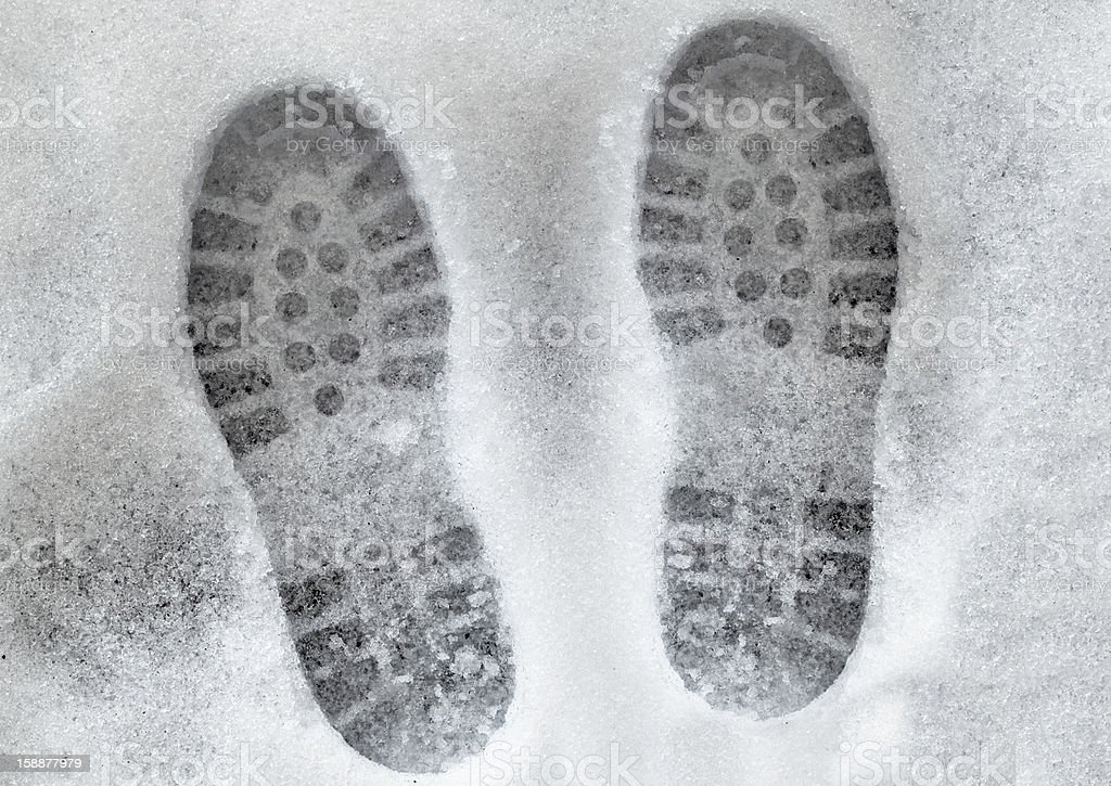 shoe prints in melting snow stock photo