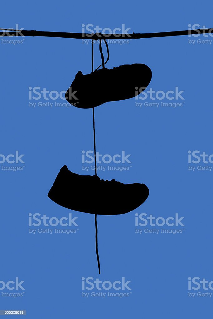 Shoefiti -  silhouette of shoes hanging over telephone cables stock photo