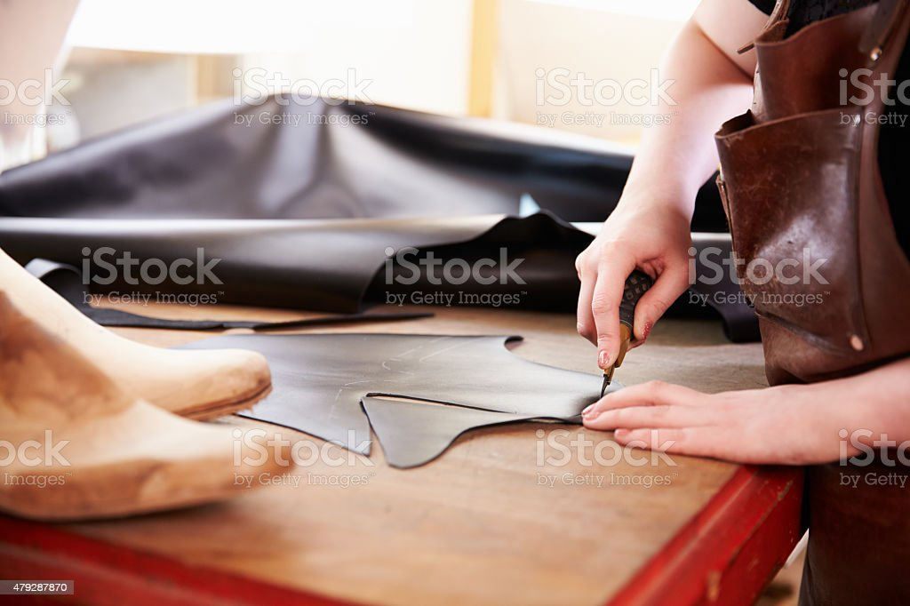 Shoemaker cutting leather in a workshop, close up stock photo