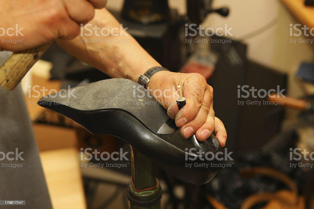 Shoemaker in his workshop repairing shoe stock photo