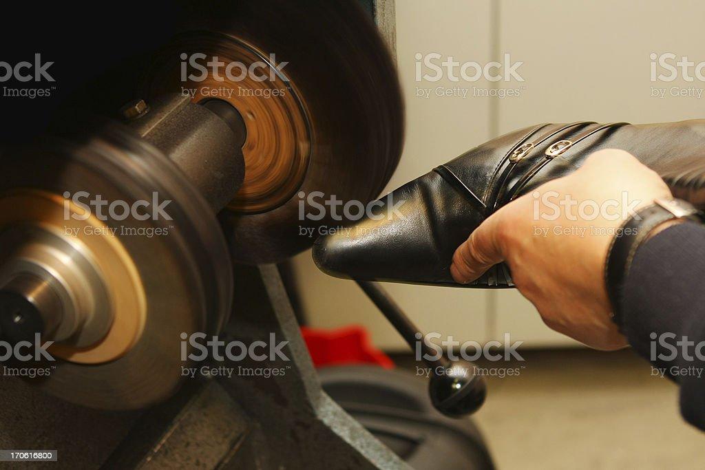 Shoemaker polishing sole of shoe royalty-free stock photo