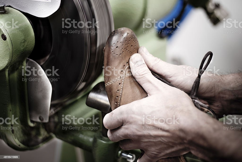 Shoemaker polishing sole of shoe stock photo