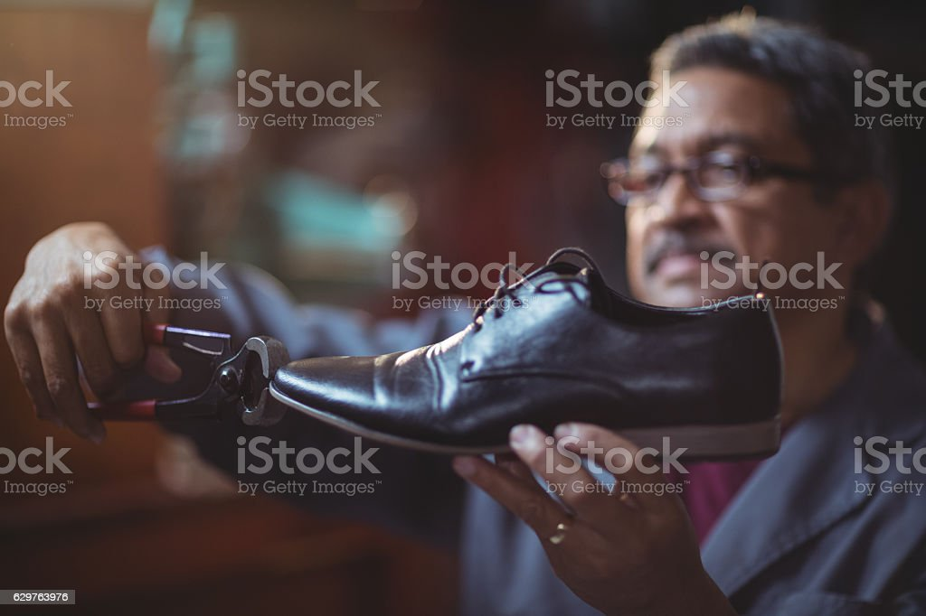 Shoemaker repairing a shoe stock photo