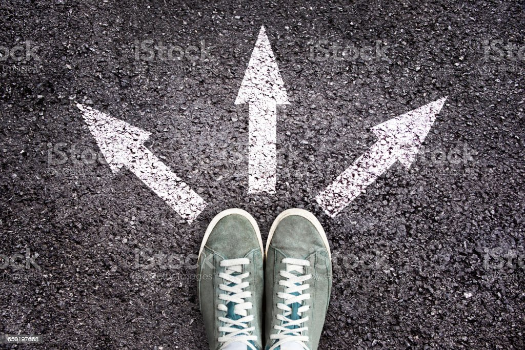 Shoes and arrows pointing in different directions on asphalt floor stock photo